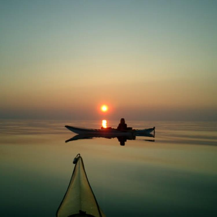 Canoe North Adventures paddler on a serene lake with the sunset in the horizon in Hay River Northwest Territories.
