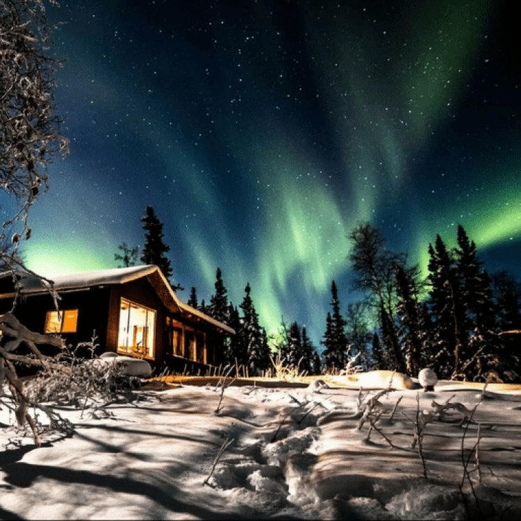The green aurora dancing in the sky above the Raven Tours cabin in Yellowknife, NWT in the winter.