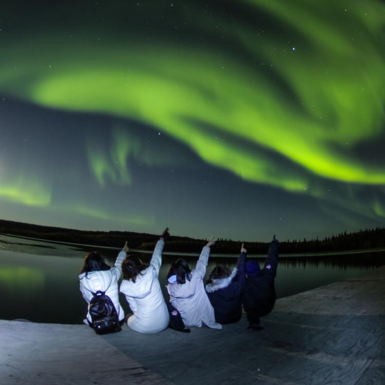 Arctic Tours Canada five people sitting at edge of a lake pointing to the sky as the green aurora northern lights dance overhead at night in Yellowknife, Northwest Territories