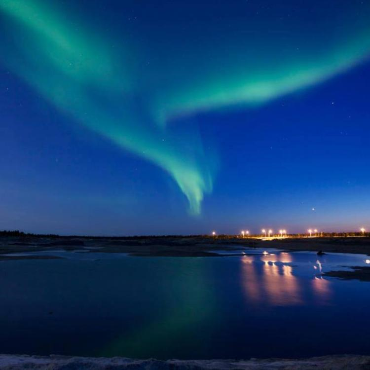 Morning Star Travel green aurora in the dark blue sky over a brightly lit city in the Northwest Territories.
