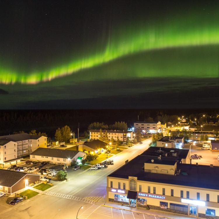 The brightly lit town of Hay River aerial view at night with the green aurora across the sky in the NWT.