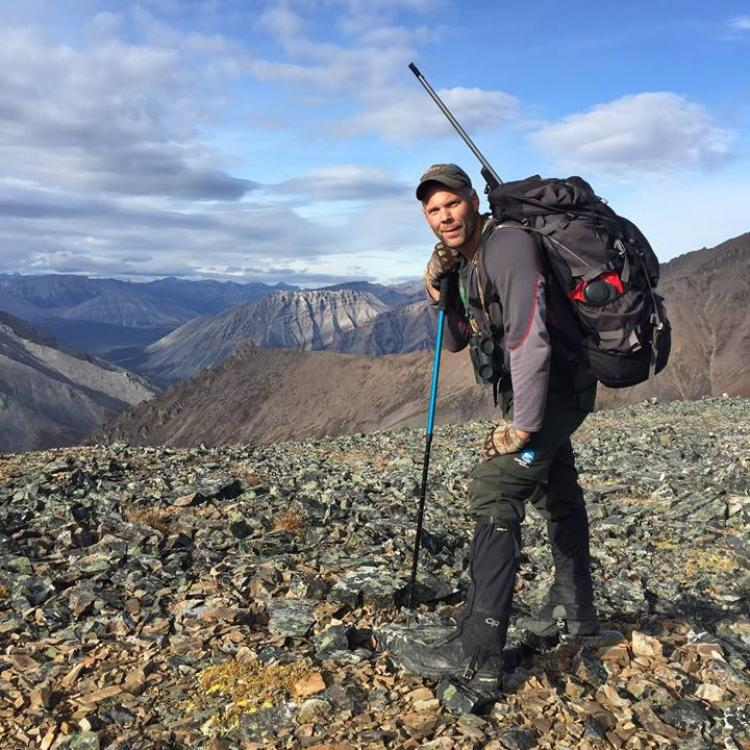 TrailBlazer Tours man hiking the Mackenzie Mountains carrying a large backpack in the Northwest Territories.