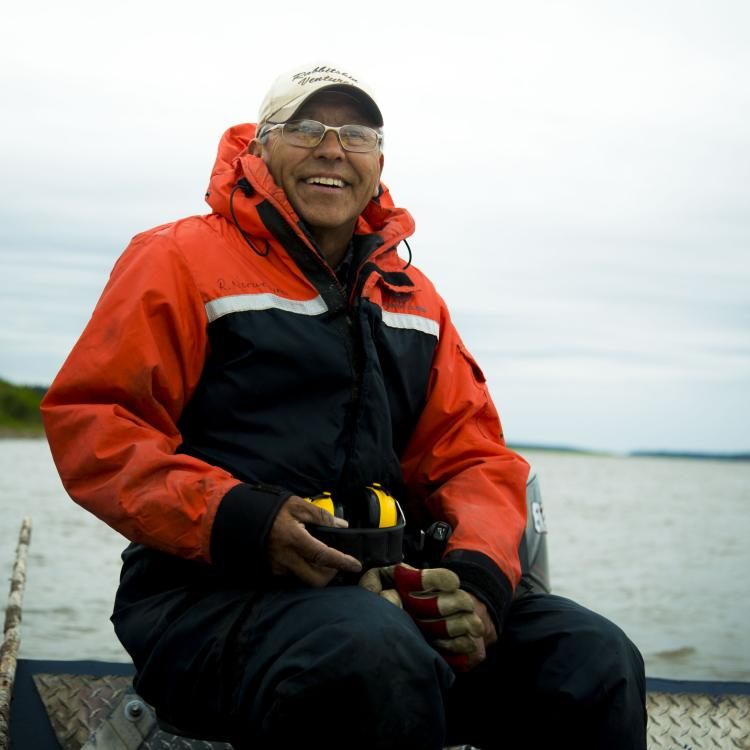 Bobby Norwegian Indigenous owner of Tah Chay Adventures sitting down in his orange and black parka smiling along the Mackenzie River in Fort Simpson, NWT.