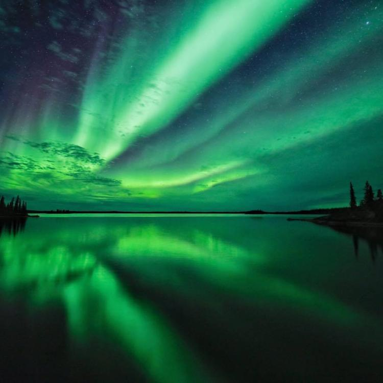Touch the Arctic Tours' picture of the green aurora shooting across the sky reflecting over the lake in Yellowknife, NWT.