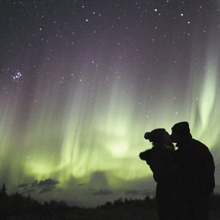 Sean Norman Aurora Chaser tourists embracing each other under the green glow of the dancing aurora northern lights in Yellowknife, Northwest Territories.