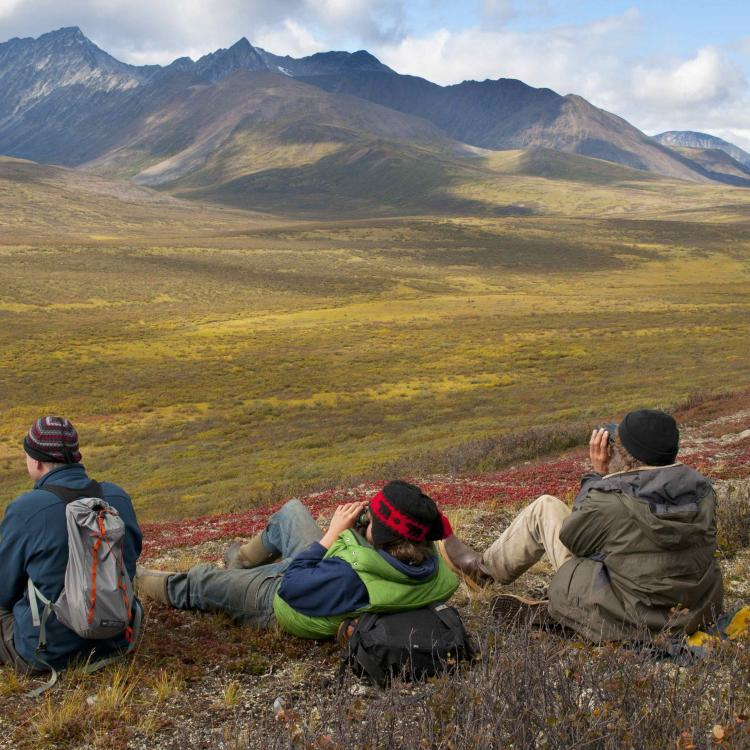 Three hikers resting on a hill overlooking mountains near Dechenla Wilderness Lodge in the NWT