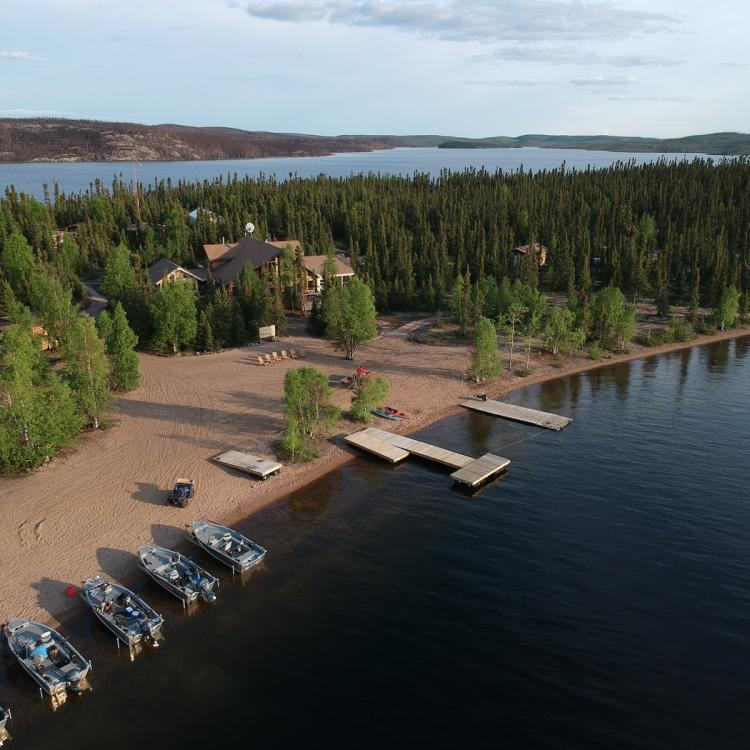 Ena Lake Lodge and lake aerial view on a sunny day at the 60th Parallel with boats parked along shore.