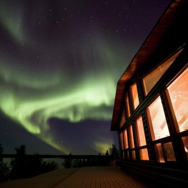 Scott Lake Lodge brightly lit under the dark sky with green aurora dancing overhead at border of the NWT and Saskatchewan.