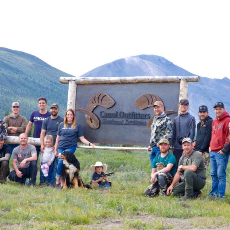Family and friends gathered around Canol Outfitters sign in the Sahtu.