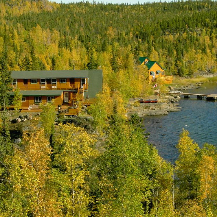 Yellow Dog Lodge aerial view among trees on a bright sunny day along the Duncan and Graham lakes in the Northwest Territories.