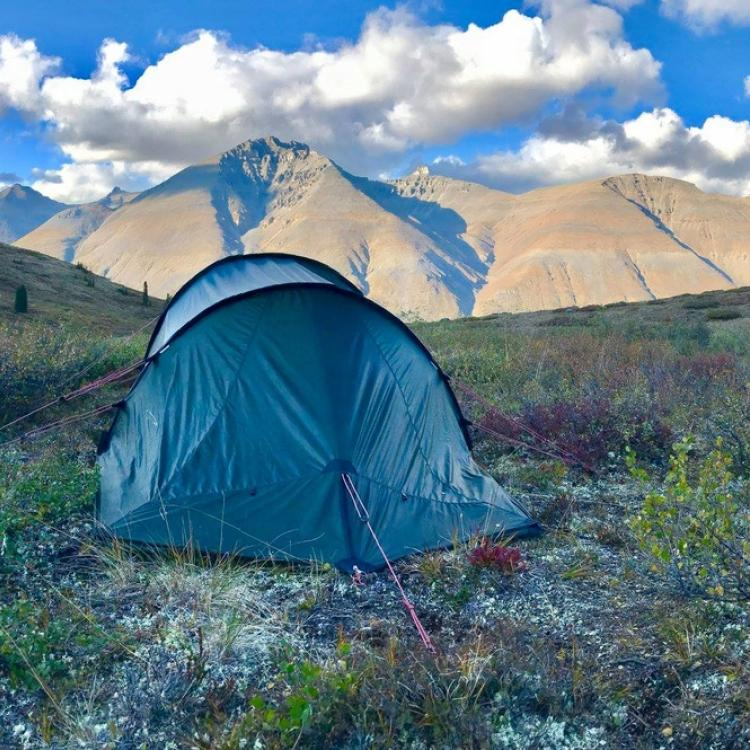 A blue tent set up in the Mackenzie Mountains in the Northwest Territories, Canada.