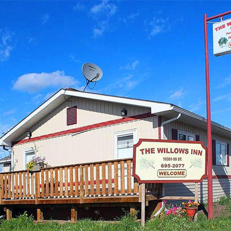 Willows Inn exterior view of motel on a sunny day in Fort Simpson, NWT.