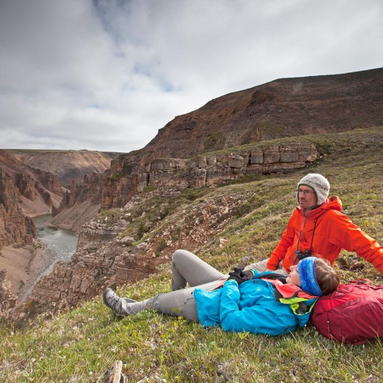 Two people laying down and admiring Tuktut Nogait National Park.
