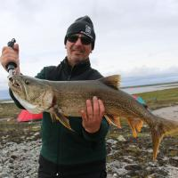 A man smiling and holding a large fish caught on a Jackpine Paddle - Thelon River trip in the Northwest Territories.