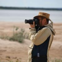 Side view of a photographer taking a photo along the sandy banks of the Thelon River on a Jack Pine Paddling trip.