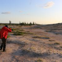 A person wearing a red coat walking along the banks of the Thelon River on a Jackpine Paddling trip.