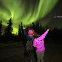 North Star Adventures two people hands up to the green aurora dancing in the sky in Yellowknife, NWT.