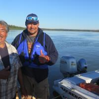 North Star Adventures Joe Bailey with an Indigenous man by a boat on the Mackenzie River in Dehcho Region NWT.