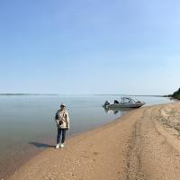 North Star Adventures a woman standing on a beach by a speed boat by the Mackenzie River in NWT.
