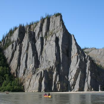 paddling past cliffs on the Mountain River, NWT, with Black Feather