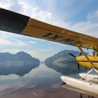 A float plane docked at Cli Lake facing two mountains in the Dehcho Region of the NWT