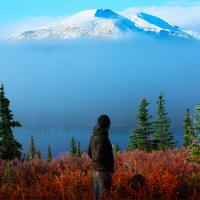 Man looking at the stunning Mackenzie Mountains clouded with some fog on a sunny day at Ten Stone Mountain Lodge.