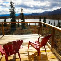 Two red lawn chairs on the deck at Ten Stone Mountain lodge with view of the lake in the Sahtu, NWT.