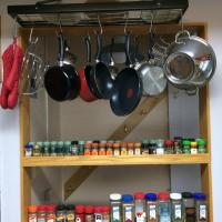 An array of pot and pans in Tiga Bed and Breakfast hanging from the wall and a line up of spices in Yellowknife, NWT.