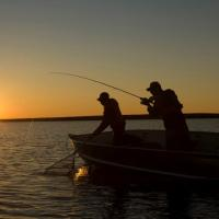 Fishing from a boat under the midnight sun in Great Bear Lake, Deline, NWT.