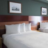 Slave Lake Inn's twin bedroom with white sheets and a dark green wall in Yellowknife, Northwest Territories.