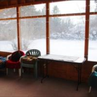 The tall glass windows of a Whispering Pines Cottage on a snowy day in the NWT.