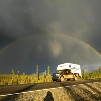 Camper Fraserway Rentals RV driving in a cloudy dark sky with a rainbow in the Northwest Territories.