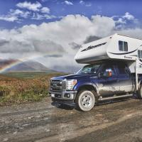 Fraserway Camper on truck driving on a gravel road in the Northwest Territories.