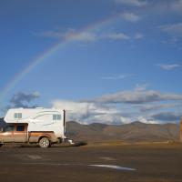 Fraser RV Camper on a truck driving with a rainbow in the sky in the Northwest Territories.