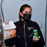 An Air North Yukon's Airline staff holding up lunch and a drink as part of their in flight food service