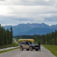 A man leans on a SUV with canoe on the roof and enjoys the view of the mountains in the Decho region of the NWT