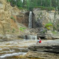A person enjoys the view of waterfalls at  Sambaa Deh Territorial Park in the NWT