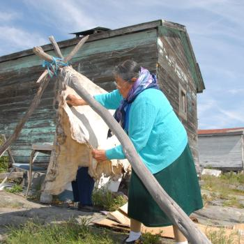a woman scrapes a hide in the community of Dettah in the Northwest Territories