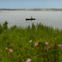 A person paddles a canoe in  Jean Marie River in the Northwest Territories
