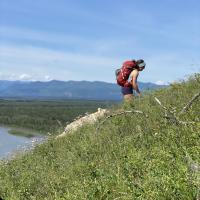 A person hiking the Nahanni Butte mountain in the Northwest territories