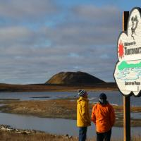 People look at a sign for the community of Tuktoyaktuk in the NWT