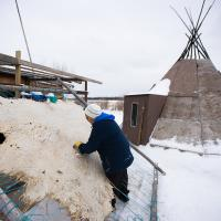 A person works on tanning a hide in  Jean Marie River in the Northwest Territories