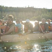 Narwal Northern Adventures paddlers in a boat in Yellowknife sunny day in the NWT.