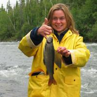 Woman with an Arctic Grayling at Watta Lake Lodge in the Northwest Territories.