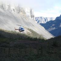 Helicopter in the sky flying in the Nahanni mountain range on a sunny day in the NWT.