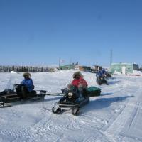 Two people skidooing snowmobiling on snow in winter on a sunny day in Inuvik Northwest Territories.