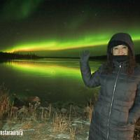 A Northern Star Tourism Services guest smiling and facing the camera with a bright yellow and green aurora behind her.
