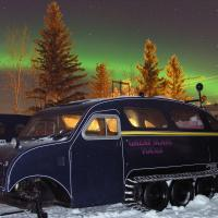 Great Slave Lake Tours Bombardier snowmobile (B12) driving on snow under the green aurora dancing in the night sky in  Hay River Northwest Territories.
