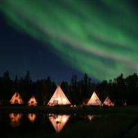 Aurora Village Northern Lights and teepees reflection on water at night green aurora in Yellowknife, NWT.