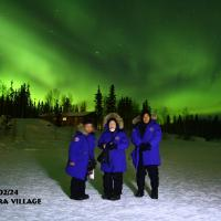Aurora Village tourists in blue parkas standing outside in winter at night with green aurora in the sky in Yellowknife, NWT.